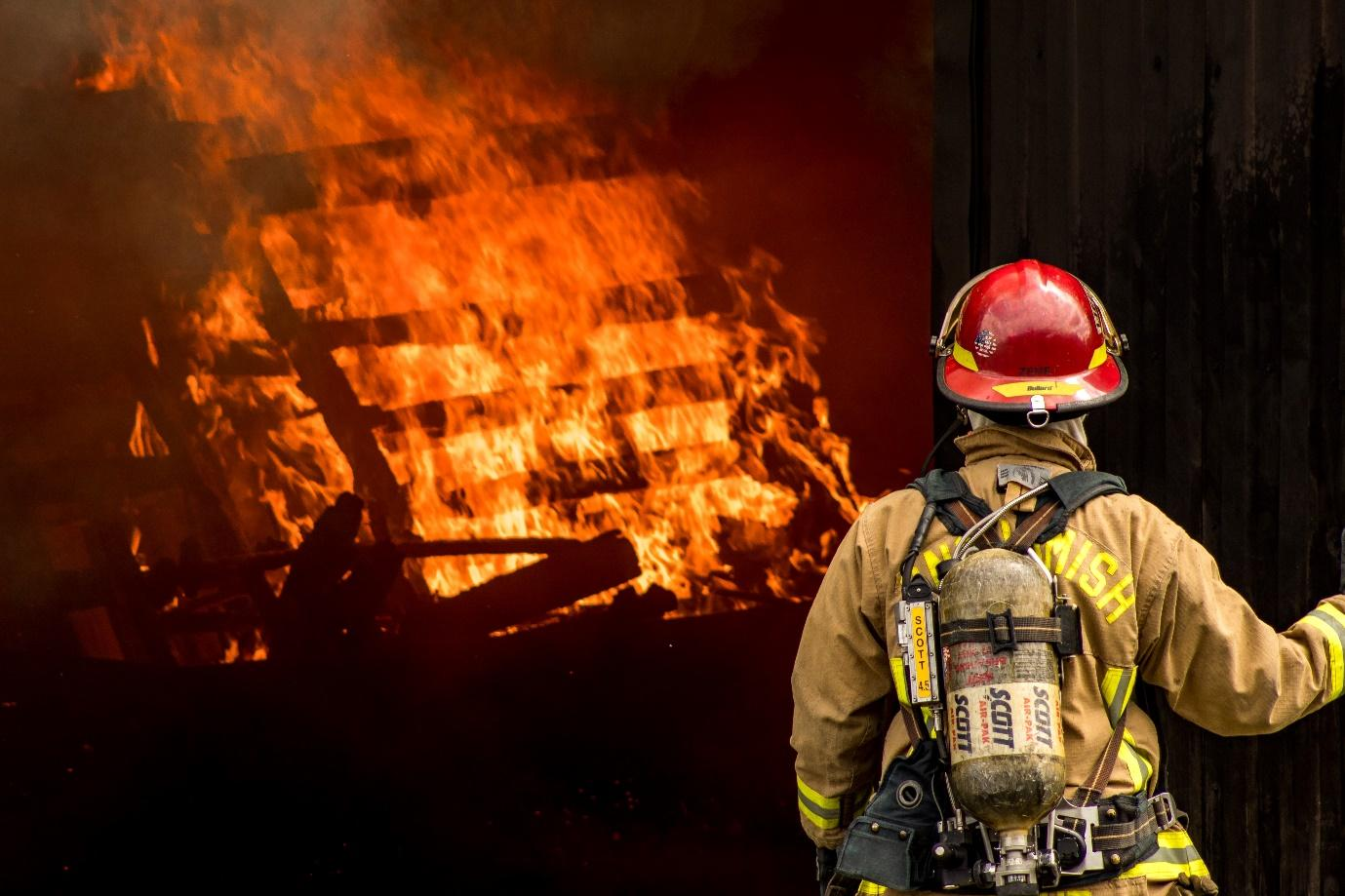 A firefighter looking at a fire Description automatically generated with low confidence